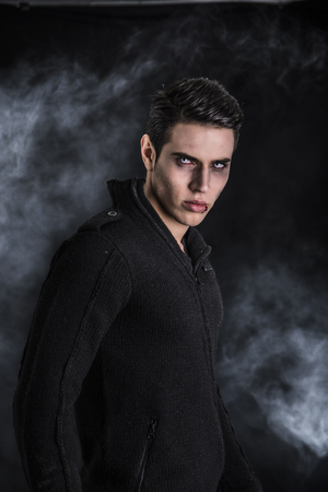 Photo pour Portrait of a Young Vampire Man with Black Sweater, Looking at the Camera, on a Dark Smoky Background. - image libre de droit