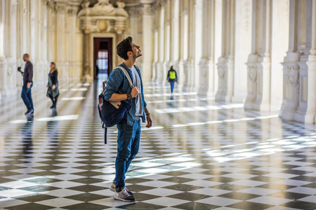 Photo pour Full Body Shot of a Thoughtful Handsome Young Man, Holding a Guide, Looking Away Inside a Museum - image libre de droit