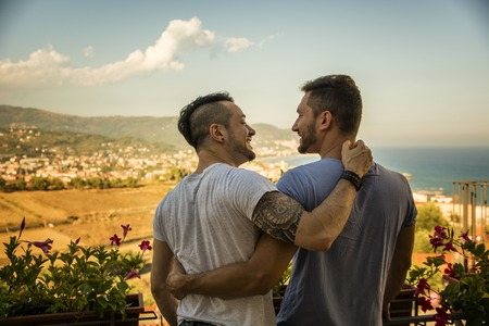 Photo for Back view of homosexual couple embracing nd looking at each other on background of resort. - Royalty Free Image