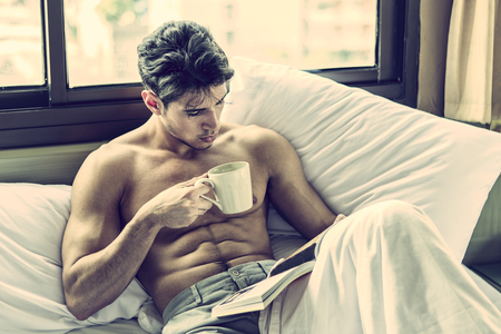 Photo for Sexy handsome young man laying shirtless on his bed next to window, holding a coffee or tea cup while reading a book - Royalty Free Image