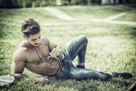Photo for Good looking, shirtless fit male model relaxing lying on the grass, shot from above - Royalty Free Image