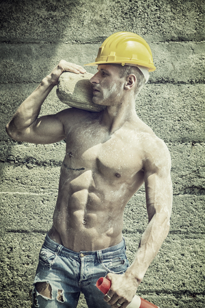 Photo pour Handsome muscular construction worker standing shirtless in front of a concrete wall, looking away to a side - image libre de droit