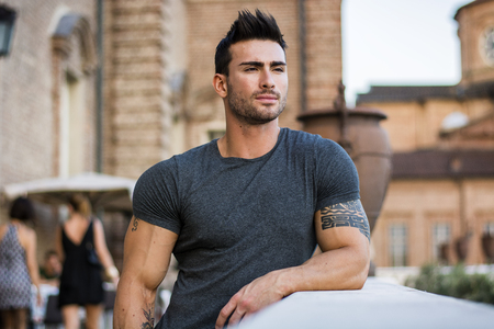 Photo for Attractaive muscular man with tattoo posing in European city center, Turin, Italy, looking at camera - Royalty Free Image