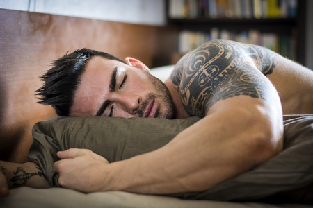 Foto de Shirtless muscular sexy male model sleeping alone on bed in his bedroom, resting - Imagen libre de derechos
