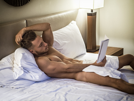 Photo pour Young shirtless muscular man lying in bed and reading a book - image libre de droit