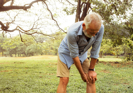 Foto de Aging man having pain in his knee on the park, Pain In The Elderly, Health care - Imagen libre de derechos