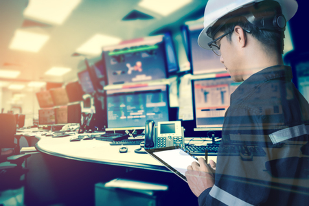 Foto de Double exposure of  Engineer or Technician man in working shirt  working with tablet in control room of oil and gas platform or plant industrial for monitor process, business and industry concept - Imagen libre de derechos