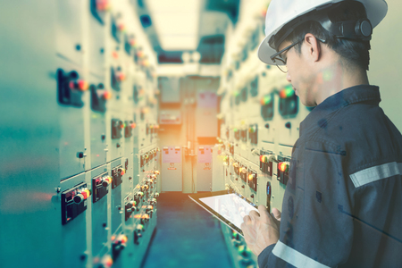 Photo pour Double exposure of  Engineer or Technician man working with tablet in switch gear electrical room of oil and gas platform or plant industrial for monitor process, business and industry concept - image libre de droit