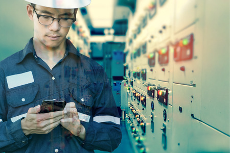 Foto für Double exposure of  Engineer or Technician man using smart phone for control electric in switch gear electrical room of oil and gas platform or plant industrial for monitor process, business and industry concept. - Lizenzfreies Bild