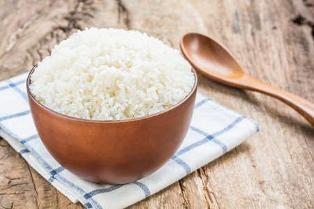 Foto de Cooked rice in bowl with spoon and dishcloth on old wooden table - Imagen libre de derechos