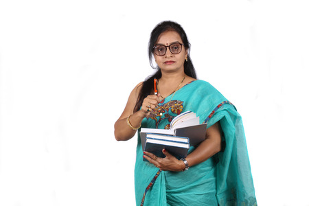 Photo pour An Indian teacher with a book and pen giving explanation, on white studio background. - image libre de droit