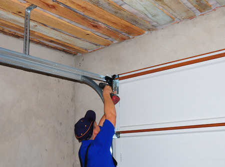 Photo pour Contractor Installing Garage Door Post Rail and Spring Installation and Garage Ceiling. Spring Tension Lifts Metal Section Garage Door Panel that the Motor does not have to Lift Entire Weight. - image libre de droit