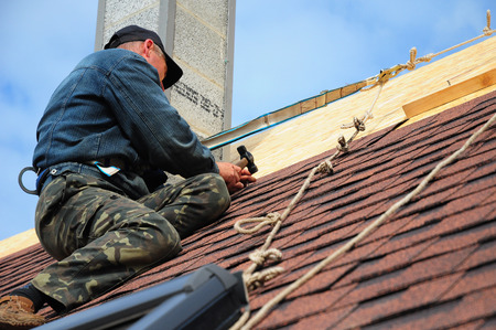 Photo pour Roofing Contractor. Roofing Construction and Building New House with Modular Chimney, Skylights, Attic  Exterior. Roofers Install, Repair Asphalt Shingles or Bitumen Tiles on the Rooftop Outdoor - image libre de droit
