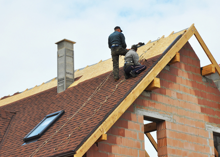 Photo pour Building contractors putting the asphalt roofing. Roofers laying tiles on the roof while roofing a house outdoor. Roofers Install, Repair Asphalt Shingles or Bitumen Tiles on the Rooftop Outdoor. Roofing Construction. - image libre de droit