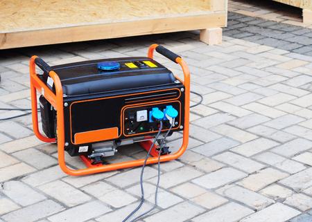 Foto de Gasoline Portable Generator on the  House Construction Site. Close up on Mobile Backup Generator .Standby Generator - Outdoor Power Equipment - Imagen libre de derechos