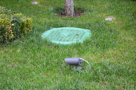 Photo pour Manhole Sewer Cover with Garden Light, Lanterns In Lawn.  Solar Powered Lamp in the garden - image libre de droit