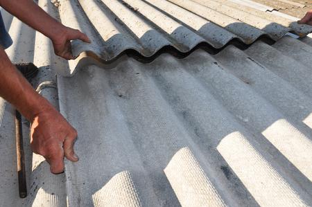 Foto de Repair dangerous asbestos old roof tiles. Worker installs asbestos roof shingles - closeup on hands. Asbestos has not been used in domestic building materials since the 1980. - Imagen libre de derechos