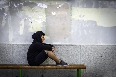 Photo pour Little boy sad sitting alone at school hides his face - image libre de droit