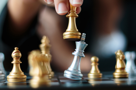 Foto de Close up shot hand of business woman moving golden chess to defeat and kill silver king chess on white and black chess board for business challenge competition winner and loser concept, selective focus on king chess shallow depth of field - Imagen libre de derechos