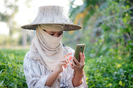 Foto de Close up shot farmer using mobile smartphone in the nature farm with ambient light - Imagen libre de derechos