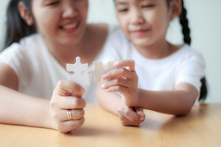 Photo for Asian little girl playing jigsaw puzzle with her mother for family concept shallow depth of field select focus on hands - Royalty Free Image