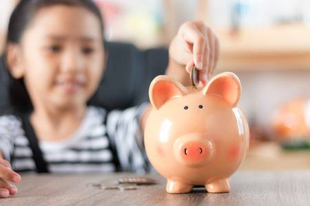 Photo for Asian little girl in putting coin in to piggy bank shallow depth of field select focus at the pig - Royalty Free Image