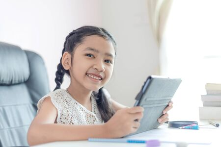 Foto de Little Asian girl using tablet and smile with happiness for education concept select focus shallow depth of field - Imagen libre de derechos