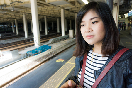 Foto per Tourist asian women waiting for train in station with bag luggage - Immagine Royalty Free