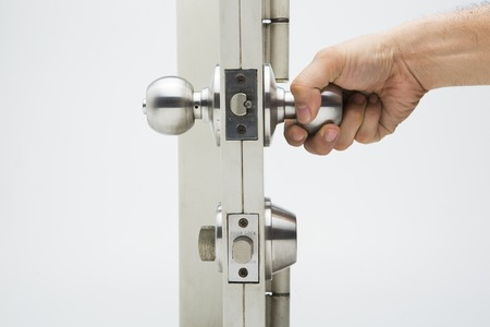 Foto de Hand hold a Door knob, aluminum door white background. - Imagen libre de derechos