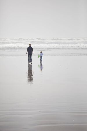 Mother and daughter walk on the beach out towards the Pacific Ocean
