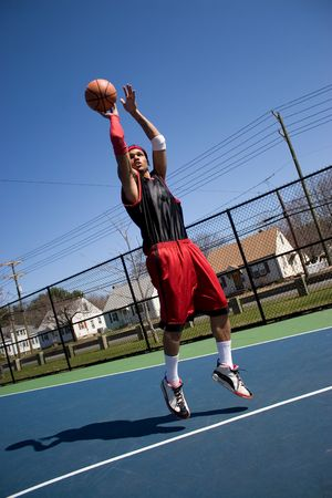 A young basketball player shooting a three point jump shot.