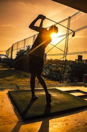Photo pour Golfer swinging in orange sunset - image libre de droit