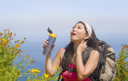Foto de young beautiful sporty Asian Korean or Chinese woman drinking water carrying big backpack trekking on beautiful beach cliff landscape in backpacker holidays trip and Summer excursion - Imagen libre de derechos