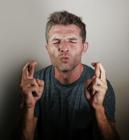Foto de portrait of young attractive wishful man crossing fingers begging and praying for good luck hoping and wishing intense isolated on even background in facial expression and emotion concept - Imagen libre de derechos