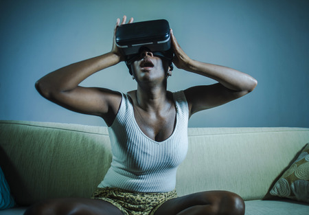 Foto de young attractive black afro American woman playing amazed and surprised virtual reality video game wearing VR goggles headset enjoying having fun at home living room couch in lifestyle concept - Imagen libre de derechos