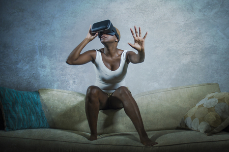 Foto de young attractive black afro American woman playing amazed and surprised virtual reality video game wearing VR goggles headset trying to touch illusion with her hand at home living room couch - Imagen libre de derechos
