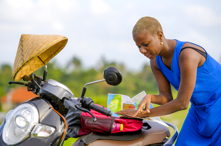 Foto de young beautiful black afro american tourist woman with scooter motorbike looking to road map searching the way exploring fields in Asia holidays summer travel and digital nomad lifestyle - Imagen libre de derechos