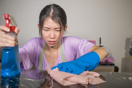Photo for young pretty overworked and sad Asian Chinese service maid woman working domestic cleaning and washing home kitchen angry upset and frustrated in housework and housekeeping stress - Royalty Free Image