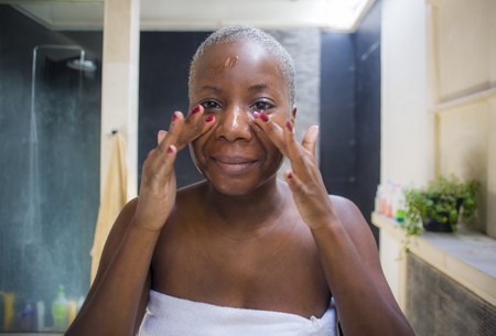 Photo pour lifestyle natural portrait of young attractive and happy black african American woman at home bathroom looking on toilet mirror applying face beauty moisturizer gel smiling fresh and cheerful - image libre de droit