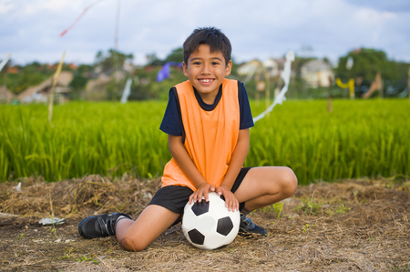 Foto de lifestyle portrait of handsome and happy young boy holding soccer ball playing football outdoors at green grass field smiling cheerful wearing training vest in kid education sport concept - Imagen libre de derechos