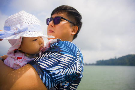 Foto de outdoors lifestyle portrait of young happy and proud Asian Chinese man as loving father holding adorable daughter baby girl during holidays excursion in family travel and tourism concept - Imagen libre de derechos