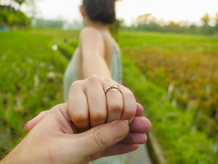 Foto de close up couple hands man holding happy fiance hand with diamond engagement ring on her finger after wedding proposal at tropical beautiful and romantic spot proposing marriage - Imagen libre de derechos