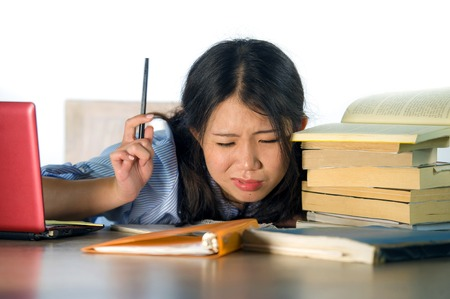 Foto per young stressed and frustrated Asian Chinese teenager student working hard with laptop computer and books pile on desk overwhelmed and exhausted feeling tired and worried isolated on white - Immagine Royalty Free