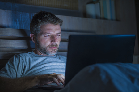Foto de young attractive and relaxed internet addict man networking concentrated late at night on bed with laptop computer in social media addiction or workaholic businessman concept - Imagen libre de derechos