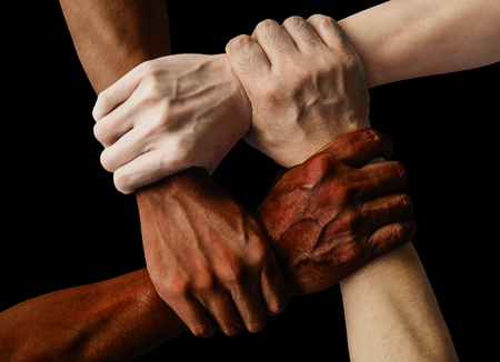 Foto de multiracial group with black african American Caucasian and Asian hands holding each other wrist in tolerance unity love and anti racism concept isolated on black background - Imagen libre de derechos