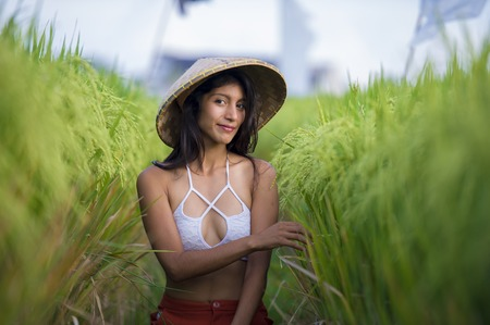Foto de young happy and beautiful latin woman playing with traditional Asian farmer hat smiling having fun posing sexy isolated on green rice field in Asia tourist trip and Summer holidays travel - Imagen libre de derechos