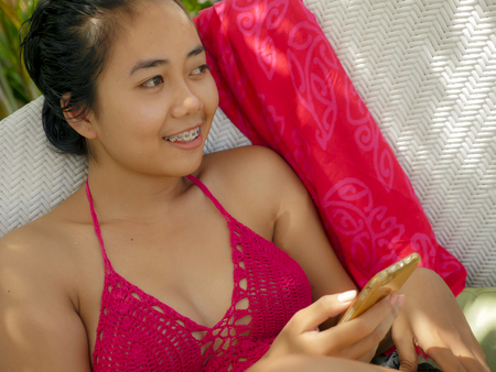 Foto de young happy and beautiful Asian Indonesian teenager girl in bikini smiling on pool bed with sarong using social media app on internet mobile phone relaxed at tropical resort enjoying Summer holidays - Imagen libre de derechos