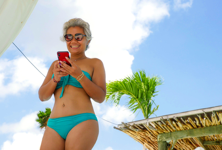 Photo pour attractive and happy Asian Indonesian middle aged 40s or 50s woman in bikini at tropical resort swimming pool using social media app on mobile phone smiling relaxed enjoying holidays trip - image libre de droit