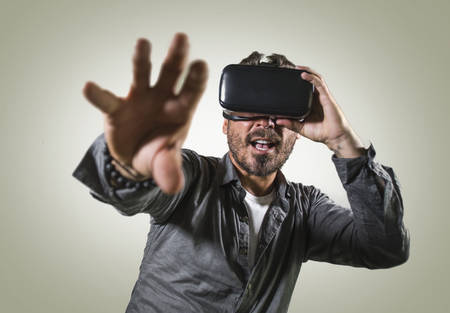 Foto de young happy and excited man wearing virtual reality VR goggles headset experimenting 3d illusion playing video game touching illusion environment surprised isolated on studio background - Imagen libre de derechos
