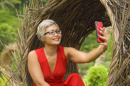 Photo for natural lifestyle portrait of attractive and happy middle aged 40s or 50s Asian woman with grey hair and stylish dress taking selfie photo with mobile phone outdoors at beautiful tropical jungle - Royalty Free Image